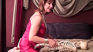 Mature Lady Brook playing with skeleton..