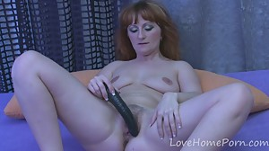 Redhead mature drills her pussy with a..